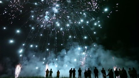 Collage of colorful fireworks exploding in the night sky with sillhouetted people in the foreground watching