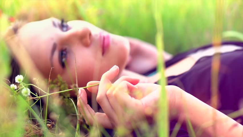 Beautiful Girl Lying on the Meadow and Dreaming. Enjoy Nature. Close up Slow Motion Footage | Shutterstock HD Video #4170274