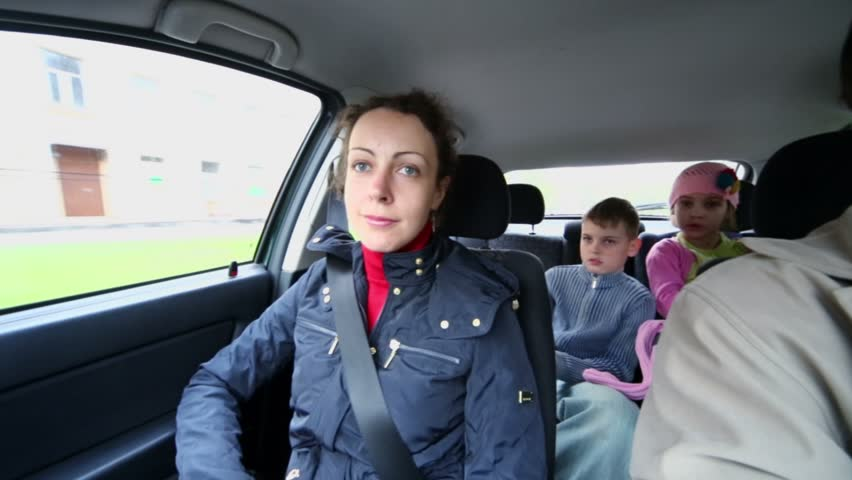 Family of four drive in car, children sit on backseat, (panoramic motion)
