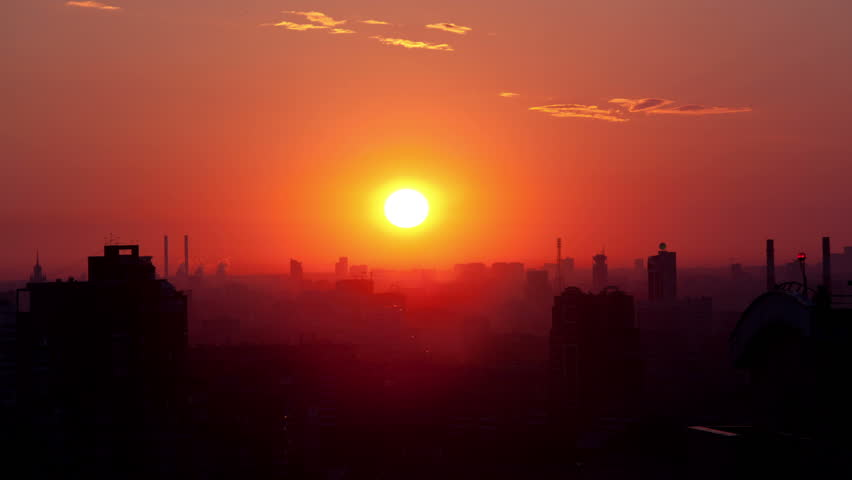 Sunrise over the city. Time lapse. High angle. Aerial view. The roofs of the houses lit by soft warm light