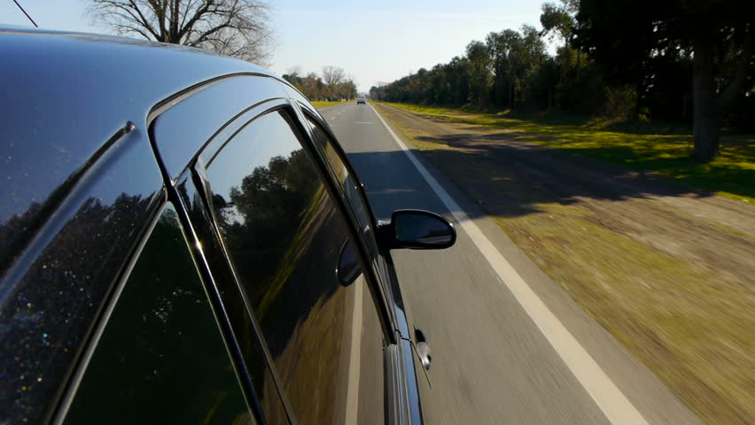 Driving a black car POV. Right side reference. Country road, trees on the side, fall, day. Slow Motion Speed. HD.