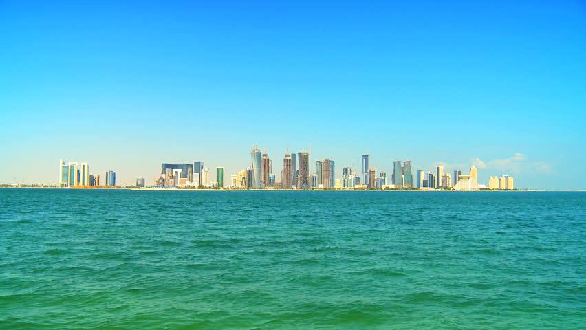 Luxury motor boat sailing waters Qatar Peninsula past skyline of modern buildings Doha, Qatar, Persian Gulf