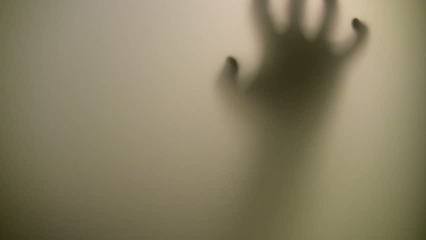 Victim. Terrified hand behind glass