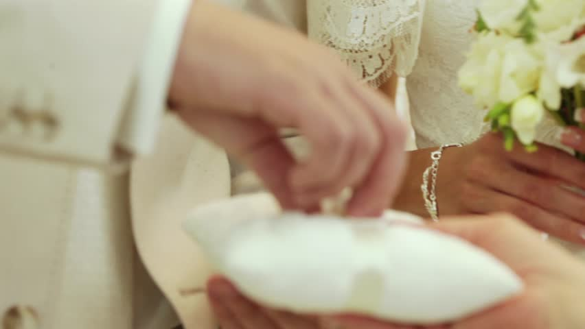 The groom wears a wedding ring is hard to hand the bride. The bride wears a ring with ease