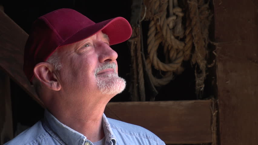 Farmer standing in a barn, close up