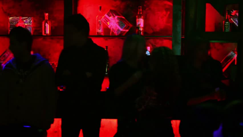 Silhouettes of several people which stands near bar with red illumination