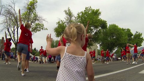 MORONI UTAH JUL 2013: Little girl waves rural small town dance team community annual 4th July parade. Families return to hometown for family fun and recreation. Granddaughter enjoying celebration.