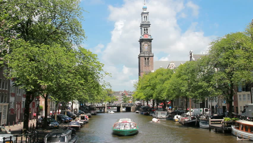 Tour boat sails in Amsterdam canal,with Westerkerk tower in the background in Amsterdam, Holland