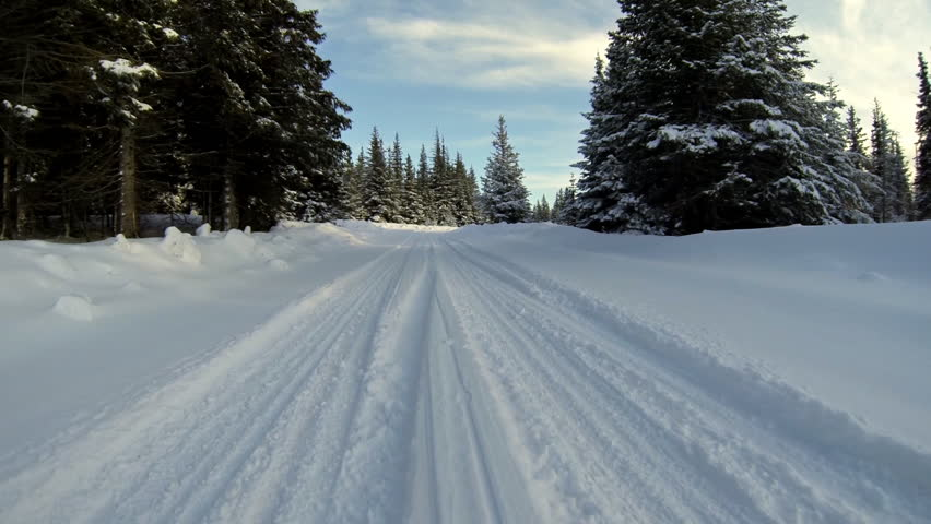Low angle driving POV on snowy country road in Alaska