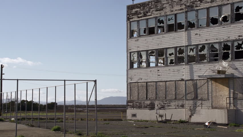 Urban cityscape of an abandoned building with broken windows and debris