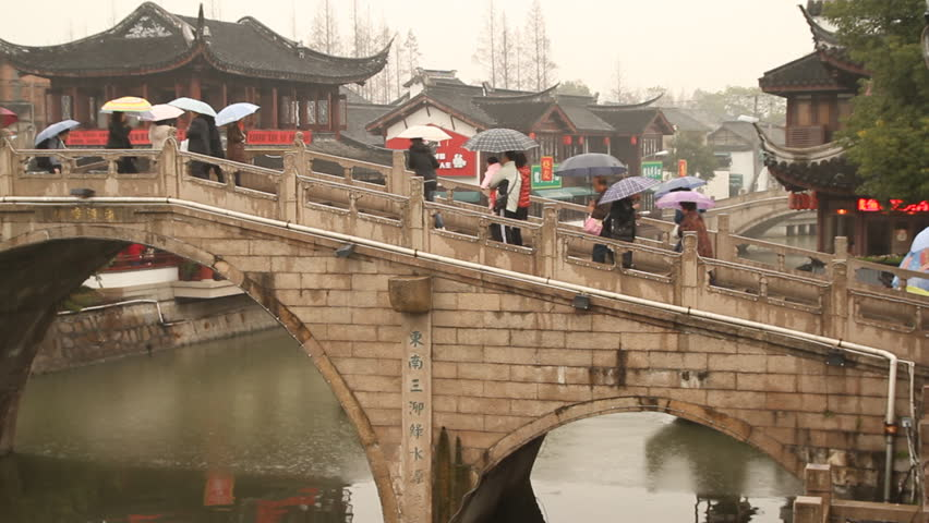 SHANGHAI - DECEMBER 16: Qibao Ancient Town stone arch bridge and boat on rainy