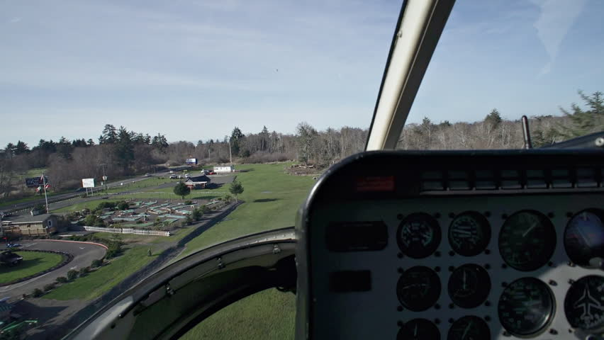 View from passenger seat of a helicopter as it flies past trees in an undefined rural area