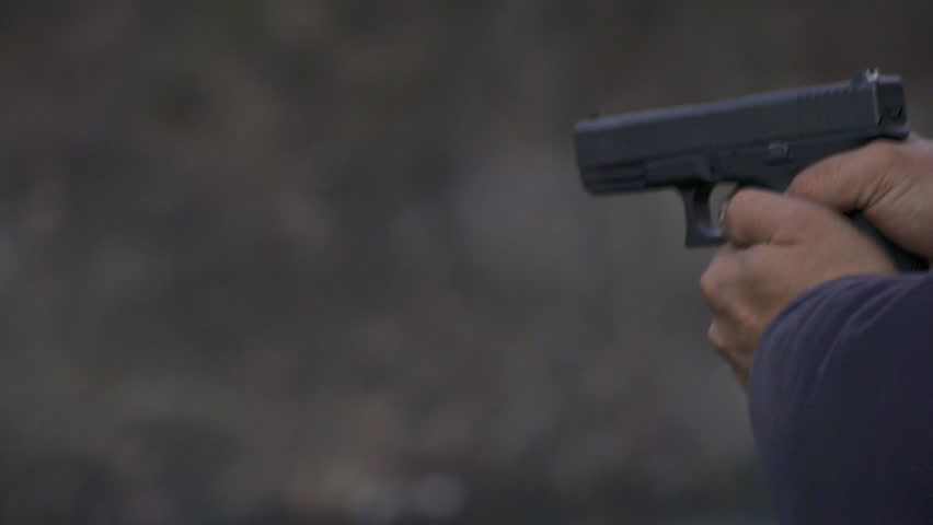 View from left of a man firing a Glock handgun repeatedly, with visible muzzle flash