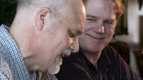 Close up on two guys talking at a bar, focus pull from foreground to background during shot.