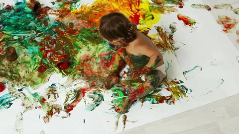 Child deliberately making an abstract painting while painting