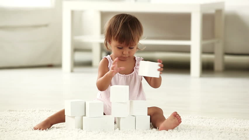 Lovely child playing with building blocks developing her creative skills