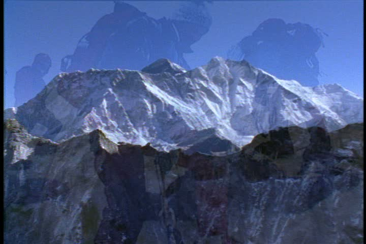 Aerial shot, slow zoom over mountain ridge to valley and WS of Mount Everest under a cloudless blue sky in Nepal.