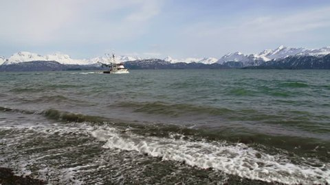 A small Alaskan fishing trawler sails across the tide in front of the stunning Kenai Mountains outside of Homer, Alaska