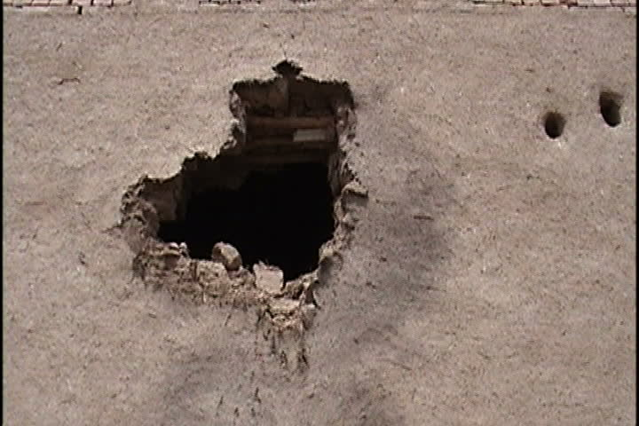 Big hole and two smaller bullet holes in mud brick building in Mir Ali, Pakistan.