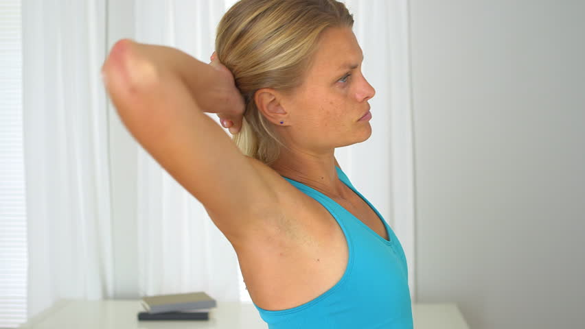 Fit blonde woman stretching at home #4359914