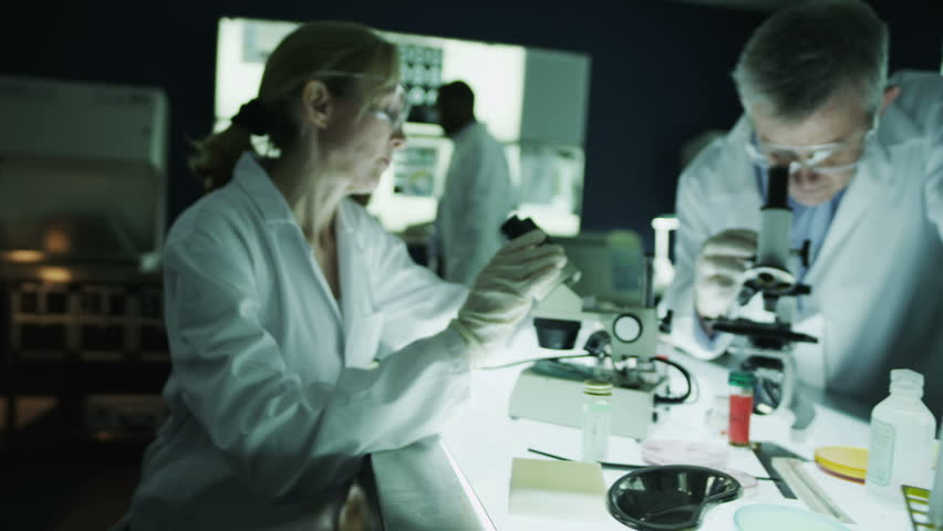 Team of scientists or researchers are working together in a dark laboratory, carrying out experiments with chemicals and a microscope. In slow motion. | Shutterstock HD Video #4362134