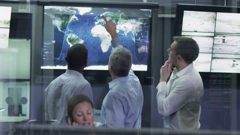 Security personnel watching the screens in a system control center. Could be a weather station or airport traffic control room. It could be a police or government surveillance facility. Slow motion.
