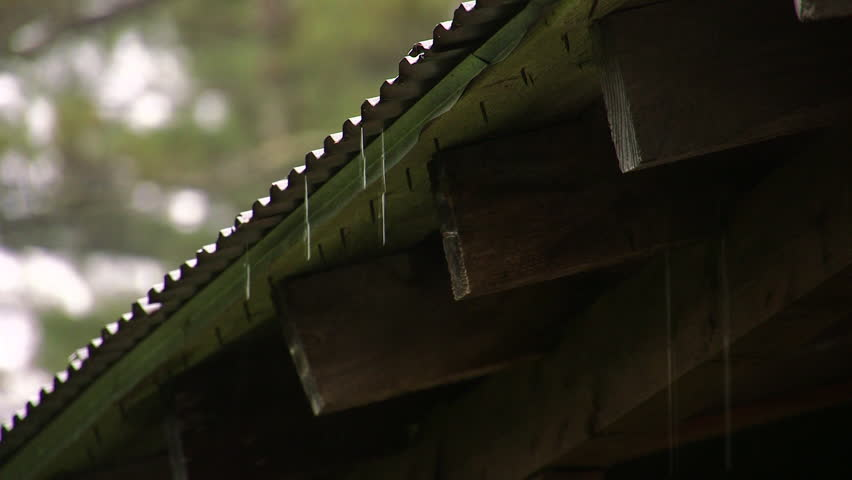 Rain water drips from the eaves of a rural wooden cabin
