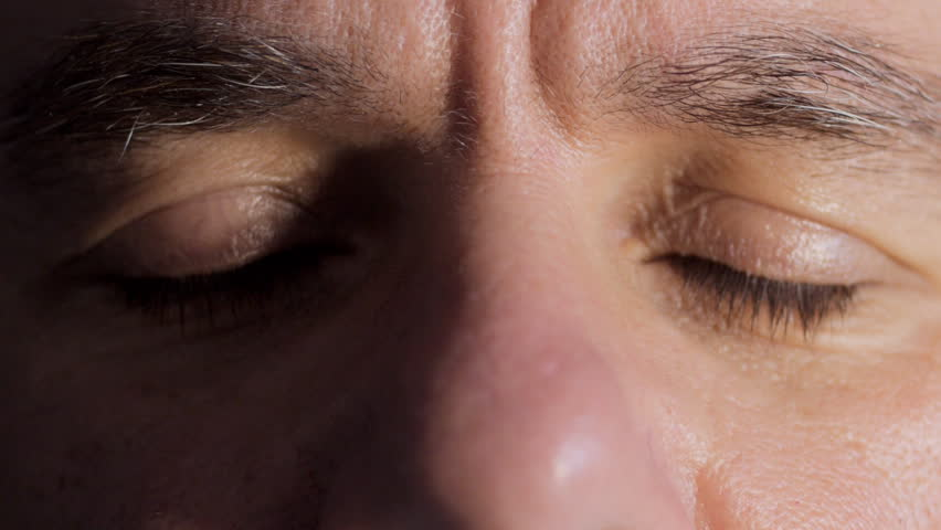 Close up of middle aged man's eyes opening