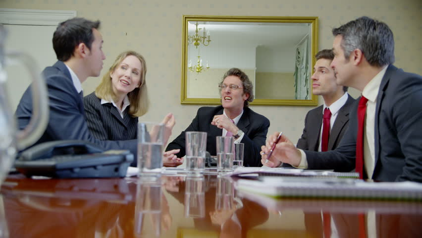 Happy mature business team are seated around a conference table for a meeting. They come to an agreement and shake hands on the deal.