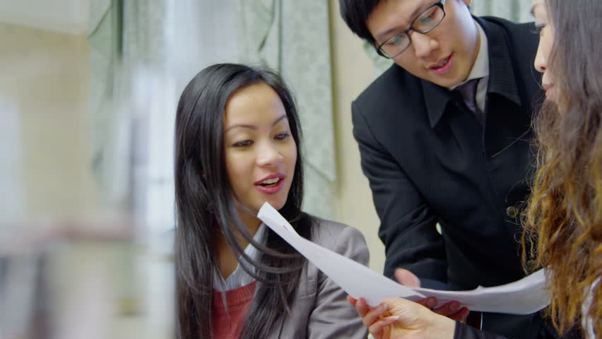 Happy and attractive young Asian business team  in a meeting in elegant office.