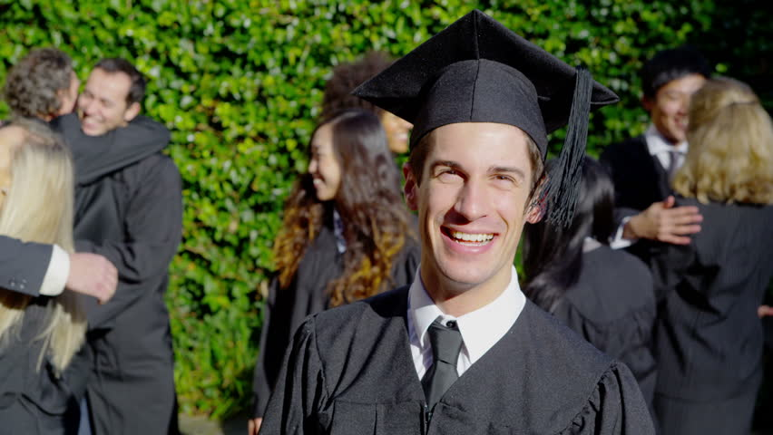 Portrait of a happy male graduate on graduation day. He smiles at the camera as his friends and their families celebrate behind him. In slow motion.