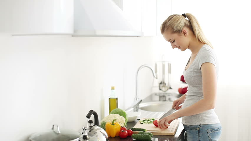Attractive young woman standing at kitchen table cutting tomatoes looking at camera and smiling