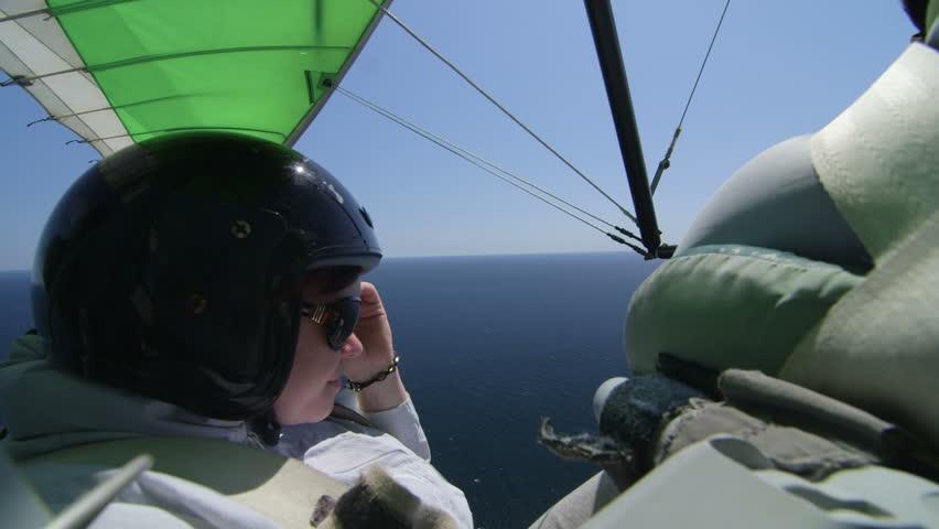 Female passenger in the back seat of motorized hang glider flying over sea