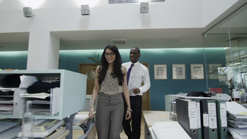 Businessman and woman talking together as they walk around a busy office with many workers. Could be collaborating on a project, or an office manager interviewing a candidate for a job. In slow motion | Shutterstock HD Video #4388147