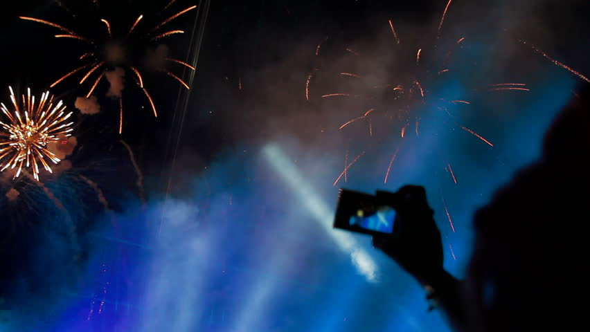 People filming beautiful festive fireworks on cameras. Fireworks in the sky.