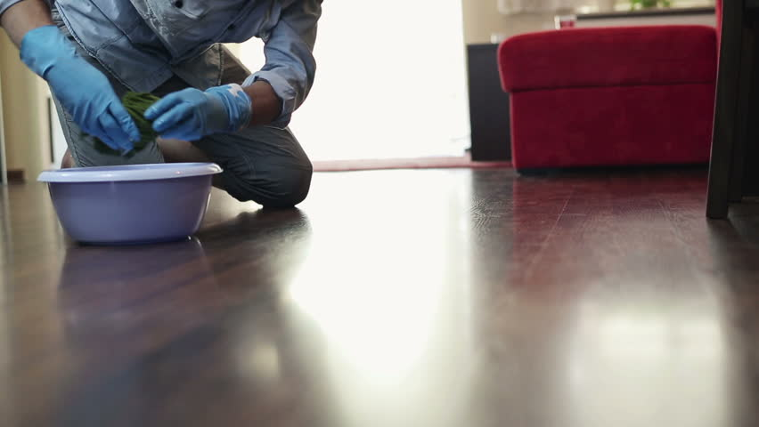 Young man cleaning wooden floor in home