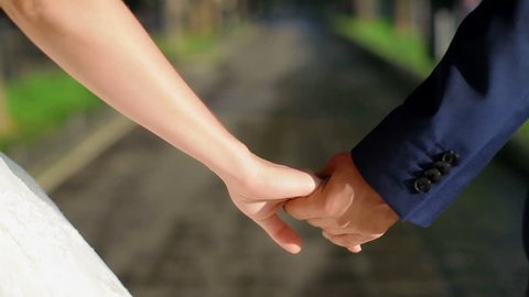 newly married couple walk together holding hands