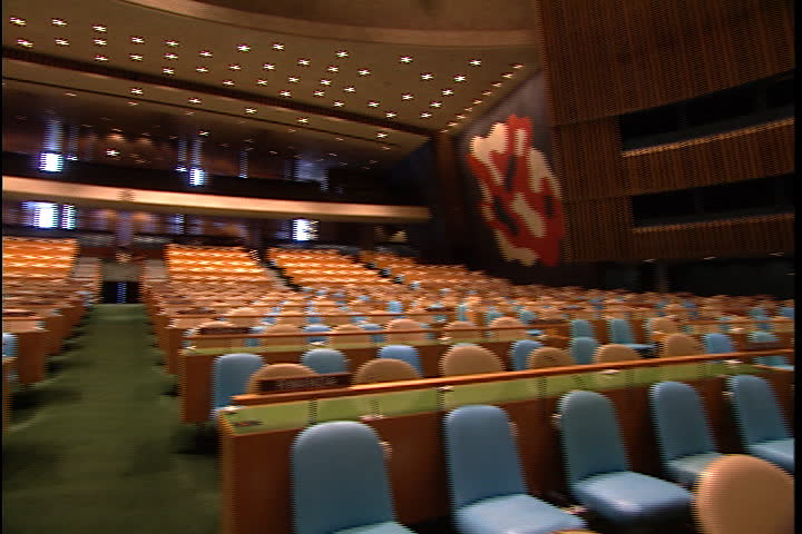 NEW YORK CITY - FEBRUARY 11, 1999: MS of the empty United Nations General Assembly hall with rows of seats: fast spinning whip pan around chamber.