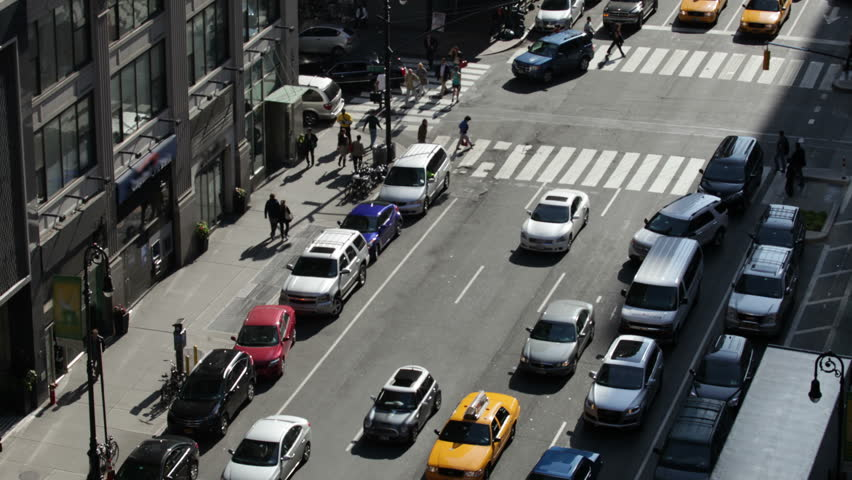 Time lapse of traffic congestion and pedestrians on a busy New York City street.