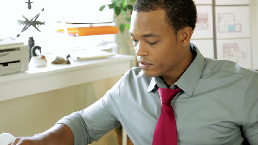 An attractive young African American architect or engineer working in his office looks up and smiles.