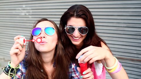 Cheerful hipster girls with sunglasses having fun making bubbles