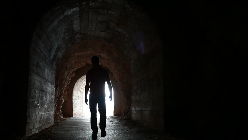 Man goes through the dark concrete tunnel into the glowing end #4436591