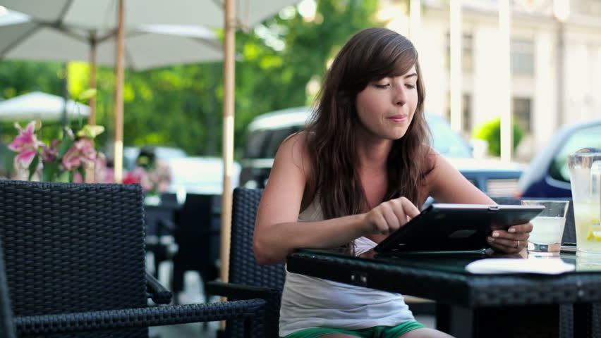 Cute young woman with tablet in cafe, steadicam shot