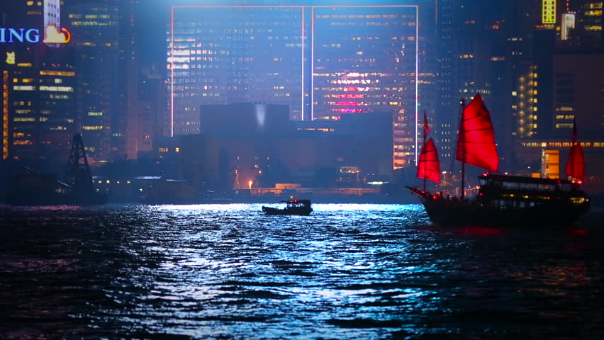 HONG KONG, 10 MAY 2013: Famous Red Sail Junk Boat passes in front of beautiful Hong Kong skyline at night, a very familiar sight.