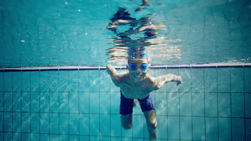 Happy cute little boy underwater is waving and smiling at the camera.