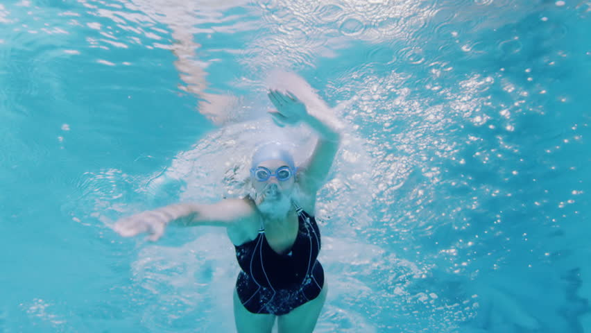 View from underneath of a professional female swimmer underwater with a bright light reflecting against the surface of the water.