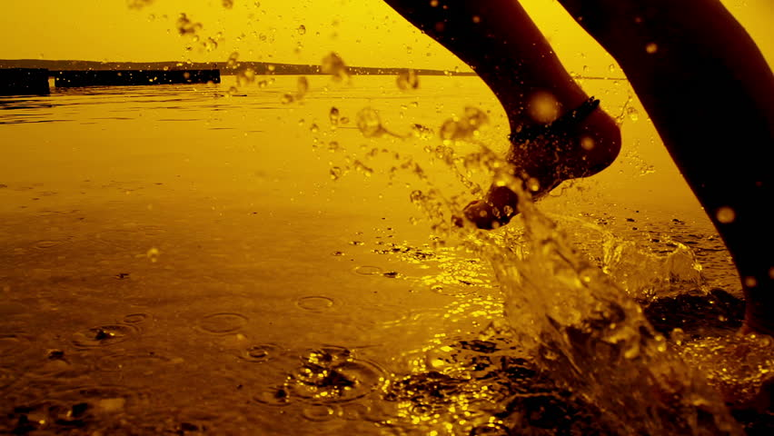 SLOW MOTION: Girl running in shallow water at sunset | Shutterstock Video #4465301
