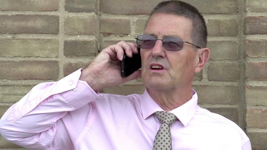 Upset elderly businessman on cell phone