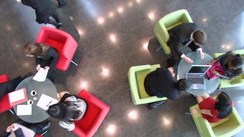 Camera crane tracks over relaxed office workers during their coffee break. Businessmen and women walk by in this large financial building. High quality HD video footage