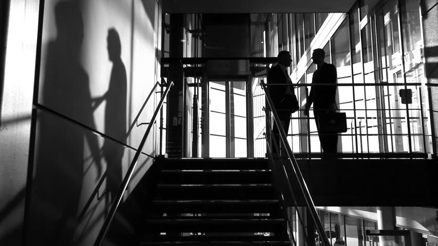 Business colleagues shake hands in this video clip of shadows meeting in large offices.